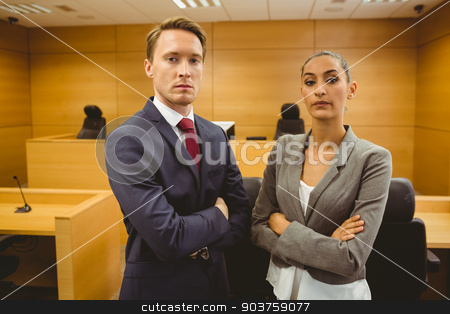 Unsmiling lawyers looking at camera crossed arms  stock photo, Unsmiling lawyers looking at camera crossed arms in the court room by Wavebreak Media