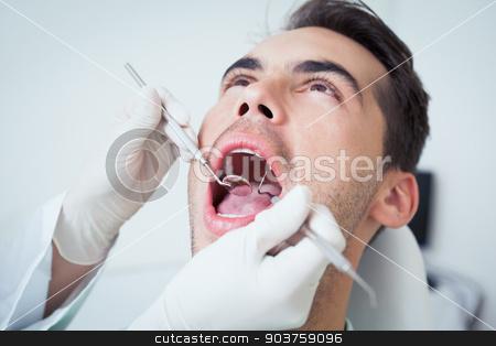 Close up of man having his teeth examined stock photo, Close up of man having his teeth examined by dentist by Wavebreak Media