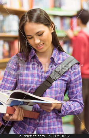 Smiling university student reading textbook stock photo, Smiling university student reading textbook in the bookcase at the university by Wavebreak Media