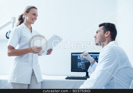 Side view of dentists discussing reports stock photo, Side view of male and female dentists discussing reports by Wavebreak Media