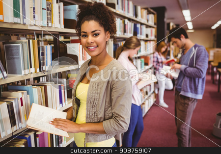 Happy student taking book from shelf stock photo, Happy student taking book from shelf in library by Wavebreak Media