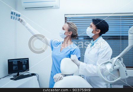 Concentrated dentists looking at x-ray stock photo, Concentrated two dentists looking at x-ray by Wavebreak Media