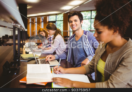 Student looking at camera while studying with classmates stock photo, Student looking at camera while studying with classmates in library by Wavebreak Media
