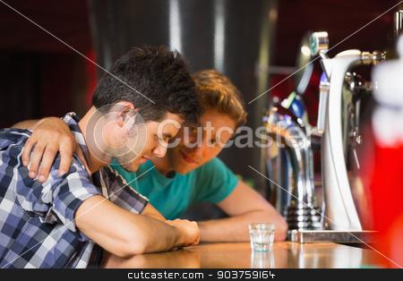 Caring friend comforting upset man  stock photo, Caring friend comforting upset man at the bar by Wavebreak Media