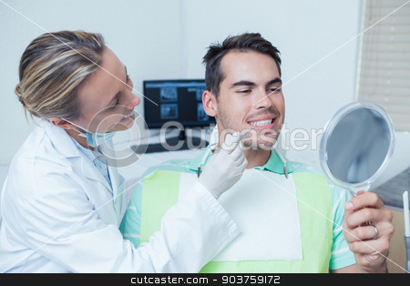 Female dentist examining mans teeth stock photo, Female dentist examining mans teeth in the dentists chair by Wavebreak Media
