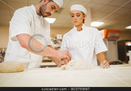 Team of bakers preparing dough stock photo, Team of bakers preparing dough in a commercial kitchen by Wavebreak Media