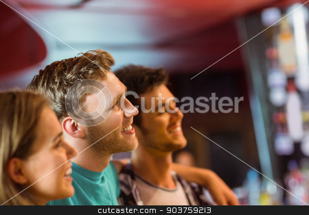 Smiling brown hair standing with arm around his friends stock photo, Smiling brown hair standing with arm around his friends in a bar by Wavebreak Media