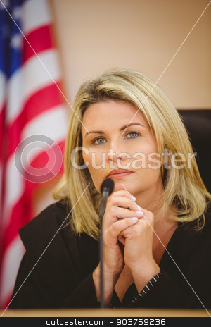 Portrait of a serious judge with american flag behind her stock photo, Portrait of a serious judge with american flag behind her in the court room by Wavebreak Media