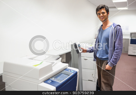 Smiling student standing next to the photocopier stock photo, Smiling student standing next to the photocopier at the university by Wavebreak Media