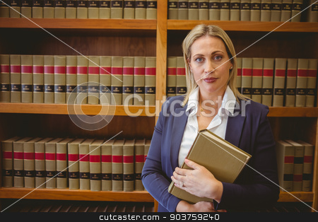 Portrait of a librarian posing and holding a book stock photo, Portrait of a librarian posing and holding a book in library by Wavebreak Media