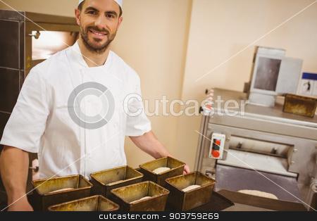 Happy baker holding tray of loaf tins stock photo, Happy baker holding tray of loaf tins in a commercial kitchen by Wavebreak Media