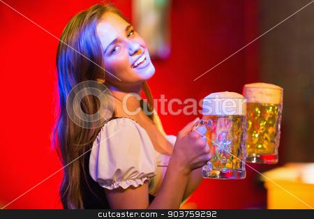 Smiling oktoberfest barmaid with beer stock photo, Smiling oktoberfest barmaid with beer at the bar by Wavebreak Media