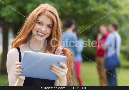 Pretty student smiling at camera using tablet pc stock photo, Pretty student smiling at camera using tablet pc at the university by Wavebreak Media