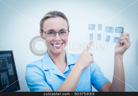 Smiling female dentist pointing at x-ray stock photo, Portrait of smiling young female dentist pointing at x-ray by Wavebreak Media