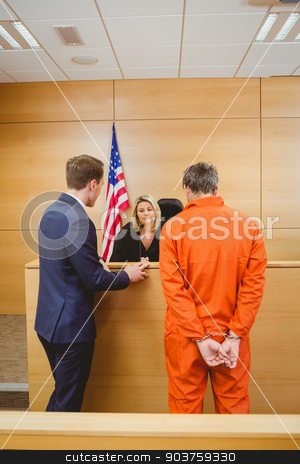 Lawyer and judge speaking next to the criminal in jumpsuit stock photo, Lawyer and judge speaking next to the criminal in jumpsuit in the court room by Wavebreak Media