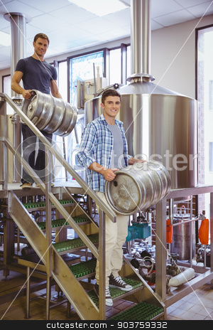 Young men carrying keg smiling at camera stock photo, Young men carrying keg smiling at camera in the factory by Wavebreak Media
