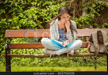Smiling student sitting on bench reading book stock photo, Smiling student sitting on bench reading book in park at school by Wavebreak Media