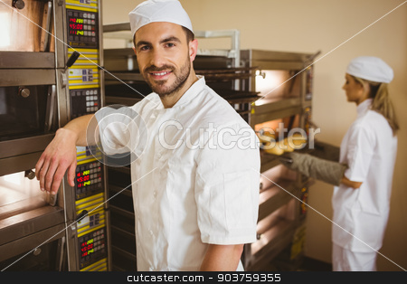 Handsome baker smiling at camera stock photo, Handsome baker smiling at camera in a commercial kitchen by Wavebreak Media