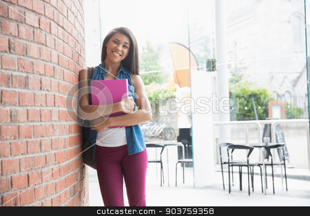Pretty student smiling and holding notepads stock photo, Pretty student smiling and holding notepads at the university by Wavebreak Media