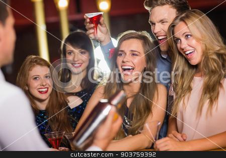 Drunk friends watching barman making cocktail stock photo, Drunk friends watching barman making cocktail at the nightclub by Wavebreak Media