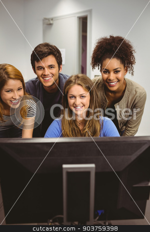 Smiling students using computer together looking at camera stock photo, Smiling students using computer together looking at camera in classroom by Wavebreak Media