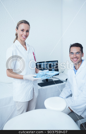 Portrait of smiling dentists with computer monitor stock photo, Portrait of smiling male and female dentists with computer monitor by Wavebreak Media