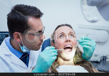 Dentist examining young womans teeth stock photo, Dentist examining young womans teeth in the dentists chair by Wavebreak Media