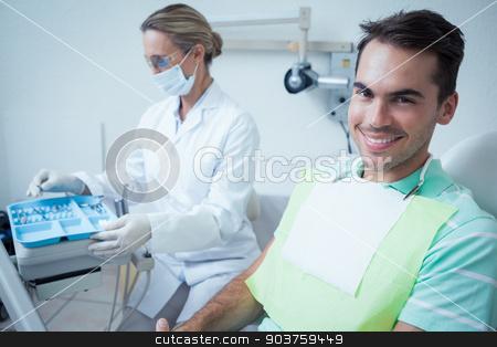 Smiling man waiting for dental exam stock photo, Portrait of smiling young man waiting for a dental exam by Wavebreak Media