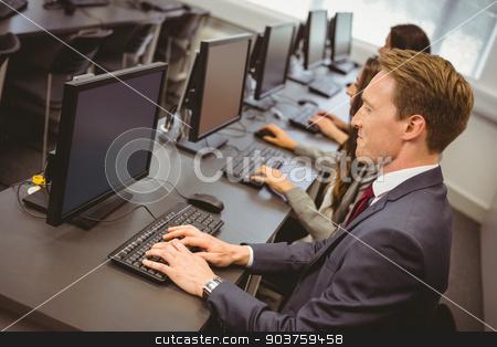 Three focused people working in computer room stock photo, Three focused people working in computer room in the office by Wavebreak Media