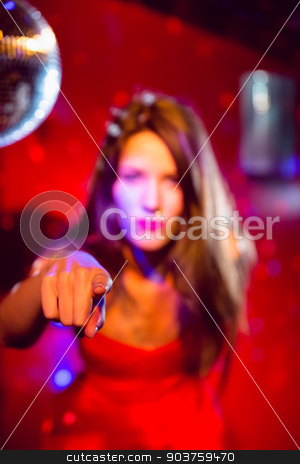 Pretty brunette dancing and pointing stock photo, Pretty brunette dancing and pointing at the nightclub  by Wavebreak Media