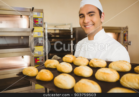 Baker smiling at camera holding tray of rolls stock photo, Baker smiling at camera holding tray of rolls in a commercial kitchen by Wavebreak Media