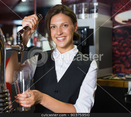 Happy barmaid pulling a pint of beer stock photo, Happy barmaid pulling a pint of beer in a bar by Wavebreak Media