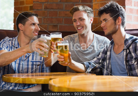 Happy friends toasting with pints of beer stock photo, Happy friends toasting with pints of beer in a bar by Wavebreak Media