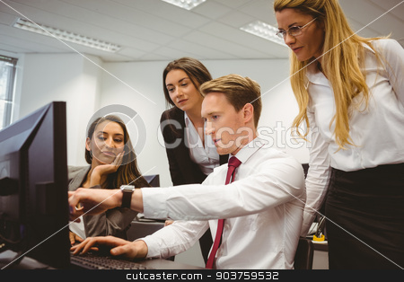Casual business team working together at desk using laptop stock photo, Casual business team working together at desk using laptop in the office by Wavebreak Media