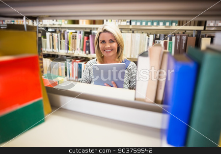 Mature student smiling in library stock photo, Mature student smiling in library at the university by Wavebreak Media