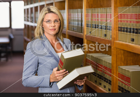 Lawyer holding books in the law library stock photo, Lawyer reading book in the law library at the university by Wavebreak Media