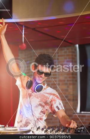 Cool dj spinning the decks stock photo, Cool dj spinning the decks at the nightclub by Wavebreak Media