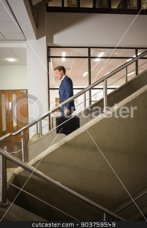 Businessman going down the stairs stock photo, Businessman going down the stairs in office building by Wavebreak Media