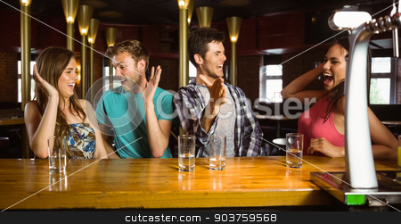 Happy friends excited for weekend activities stock photo, Happy friends excited for weekend activities in a bar by Wavebreak Media