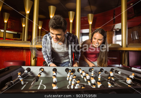 Smiling friends playing table football together  stock photo, Smiling friends playing table football together in a pub by Wavebreak Media