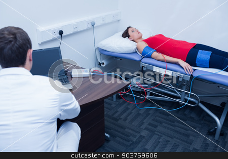 Doctor checking blood pressure of woman stock photo, Doctor checking blood pressure of woman at medical office by Wavebreak Media
