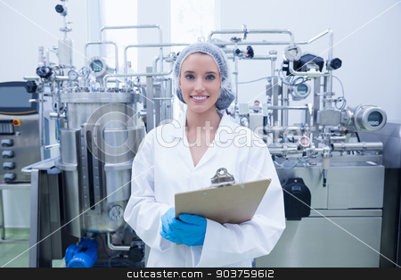 Portrait of a smiling scientist holding a clipboard stock photo, Portrait of a smiling scientist holding a clipboard in the factory by Wavebreak Media