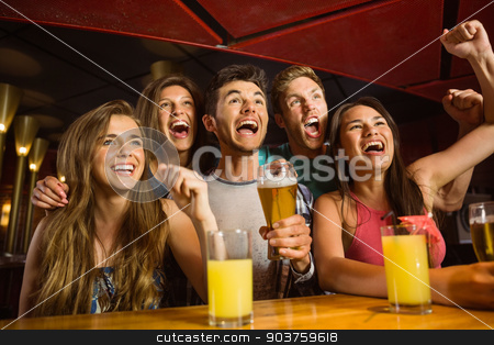 Happy friends drinking beer and cheering together stock photo, Happy friends drinking beer and cheering together in a bar by Wavebreak Media