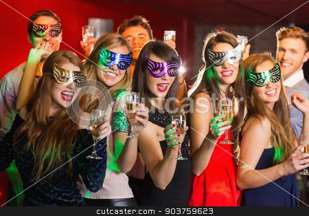 Friends in masquerade masks drinking champagne stock photo, Friends in masquerade masks drinking champagne at the nightclub by Wavebreak Media