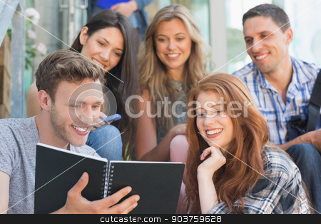 Happy students looking at book outside on campus stock photo, Happy students looking at book outside on campus at the university by Wavebreak Media