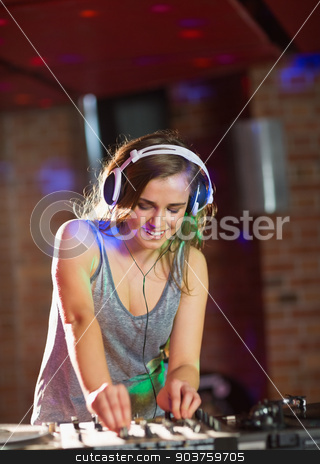 Pretty dj playing techno music stock photo, Pretty dj playing techno music at the nightclub by Wavebreak Media