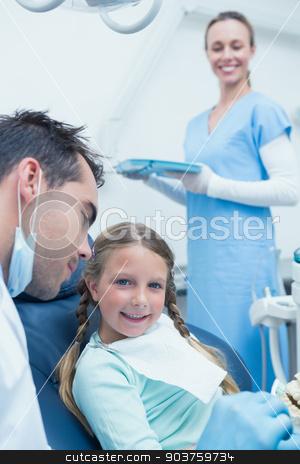Male dentist teaching girl how to brush teeth stock photo, Male dentist teaching girl how to brush teeth in the dentists chair by Wavebreak Media