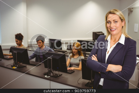 Computer teacher smiling at camera with arms crossed  stock photo, Computer teacher smiling at camera with arms crossed at the university by Wavebreak Media