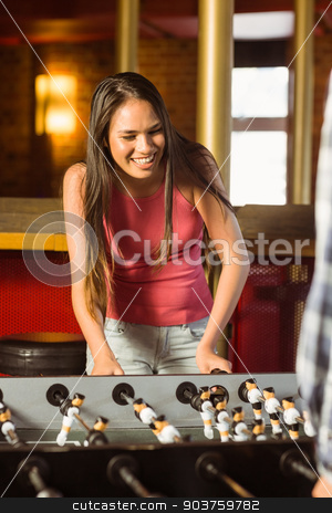 A brunette playing table football stock photo, A brunette playing table football with friends in a bar by Wavebreak Media