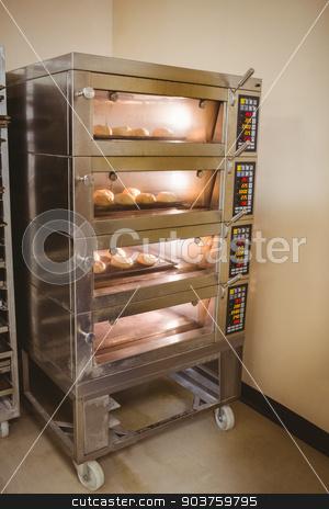 Bread rolls baking in oven stock photo, Bread rolls baking in oven in a commercial kitchen by Wavebreak Media